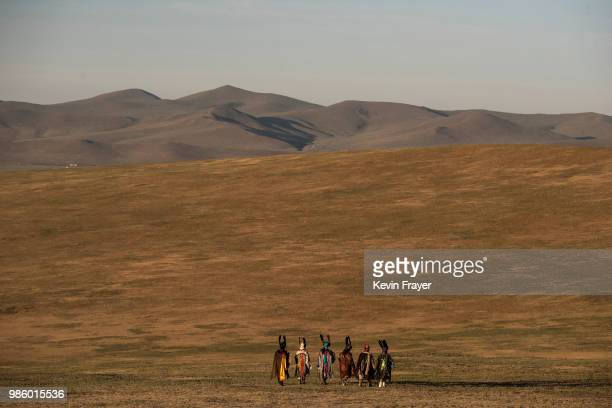 Mongolian Shamans or Buu walk away following a sun ritual ceremony to mark the period of the Summer Solstice in the grasslands at sunrise on June 22...