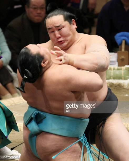 Mongolian sumo grand champion Asashoryu pushes Toyonoshima out of the ring during sixth day bout of the New Year Grand Sumo Tournament in Tokyo on...