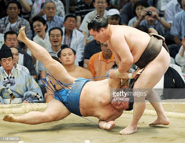 Mongolian sumo grand champion Hakuho throws Tosayutaka to the ground at the second day bout of the Nagoya Grand Sumo Tournament in Nagoya city in...
