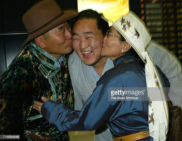 Mongolian sumo wrestler Asashoryu is kissed by his parents at Nagoya Airport on July 23 2002 in Toyoyama Aichi Japan