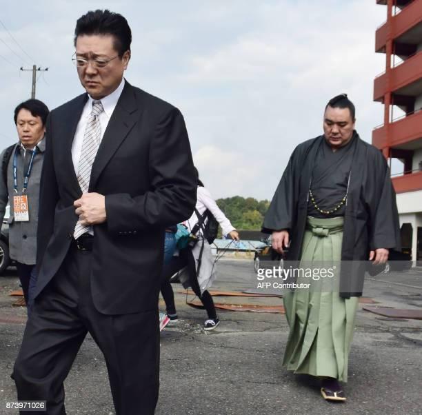 Mongolian sumo wrestler yokozuna, or grand champion, Harumafuji and stable master Isegahama walk towards a dormitory in Tagawa city, Fukuoka...