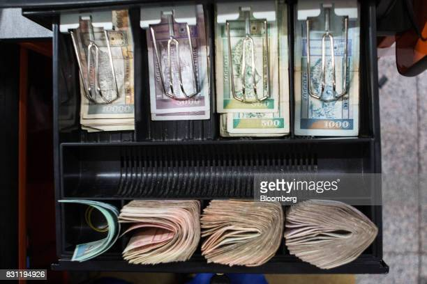 Mongolian tugrik banknotes of various denominations sit in a cash register at the checkout desk of a Nomin Holding supermarket in Ulaanbaatar...