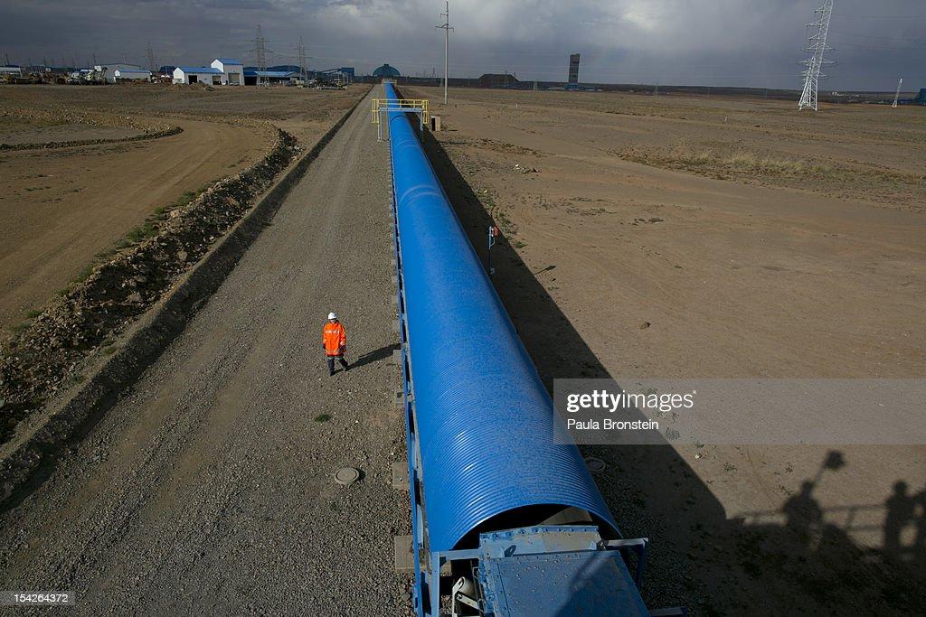 Mongolian worker walks by a blue conveyor belt that moves