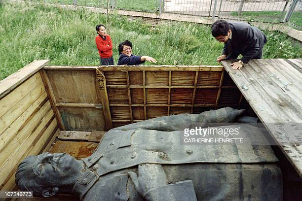 Mongolian workers look at a statue of Stalin on July 26 1990 in Mongolia that has been in storage since February when it was removed from in front of...