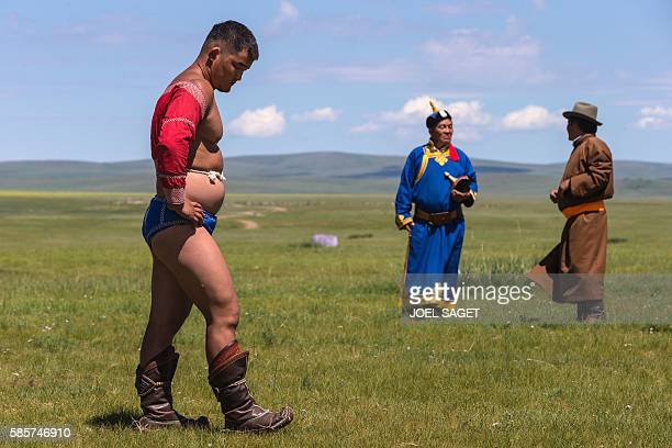 A Mongolian wrestler stands up during the traditionnal Nadaam festival in the Ovorkhangai province on July 18 2016 / AFP / JOEL SAGET