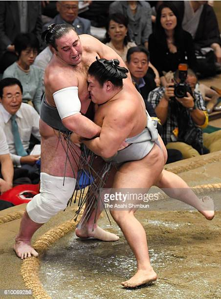 Mongolian wrestler Takanoiwa pushes Georgian wrestler Tochinoshin out of the ring to win during day ten of the Grand Sumo Autumn Tournament at...