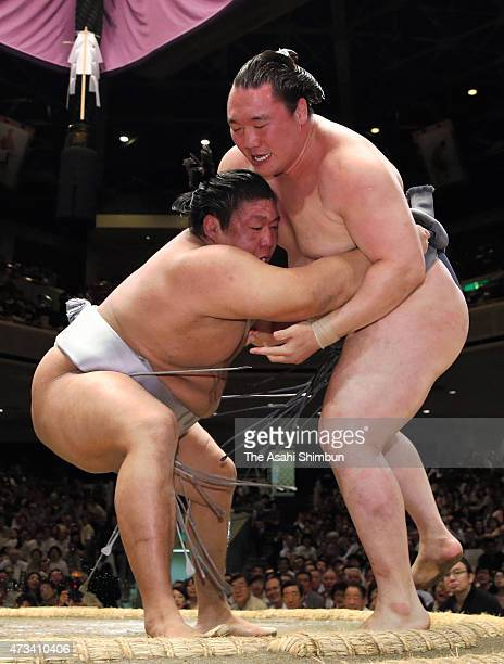 Mongolian wrestler Takanoiwa pushes his fellow wrestler Arawashi out of the ring to win in day six of the Grand Sumo Summer Tournament at Ryogoku...