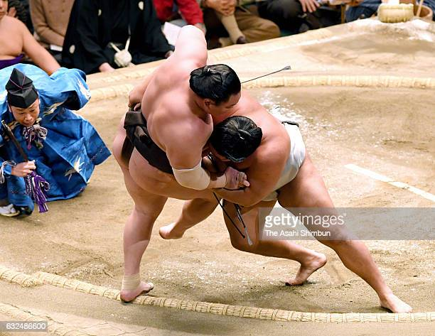Mongolian wrestler Takanoiwa pushes Mongolian yokozuna Hakuho out of the ring to win during day fourteen of the Grand Sumo New Year Tournament at...