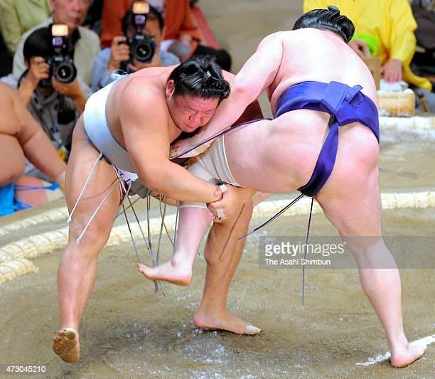 Mongolian wrestler Takanoiwa takes a leg of his fellow wrestler Seiro to throw during the day two of the Grand Sumo Summer Tournament at Ryogoku...