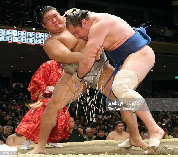Mongolian wrestler Takanoiwa to throw Russian wrestler Amuuru to win during day eleven of the Grand Sumo New Year Tournament at Ryogoku Kokugikan on...