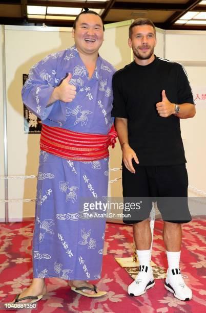 Mongolian yokozuna Hakuho and Lukas Podolski of Vissel Kobe pose for photographs on day eleven of the Grand Sumo Autumn Tournament at Ryogoku...