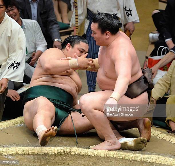 Mongolian yokozuna Hakuho gives his hand to Okinoumi after beating during day one of the Grand Sumo Summer Tournament at Ryogoku Kokugikan on May 8...