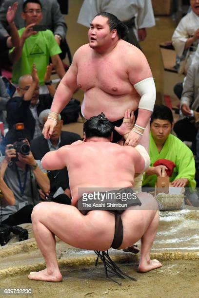 Mongolian yokozuna Hakuho pushes Mongolian ozeki Terunofuji out of the ring to win during day fourteen of the Grand Sumo Summer Tournament at Ryogoku...