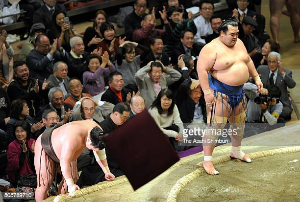 Mongolian yokozuna Hakuho reacts after his defeat to ozeki Kotoshogiku while cushions fly toward the ring during day eleven of the Grand Sumo New...