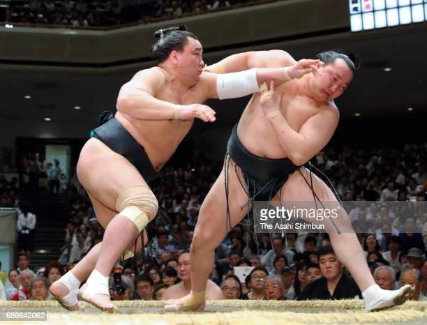 Mongolian yokozuna Harumafuji pushes Mongolian wrestler Chiyoshoma out of the ring to win during day eight of the Grand Sumo Summer Tournament at...