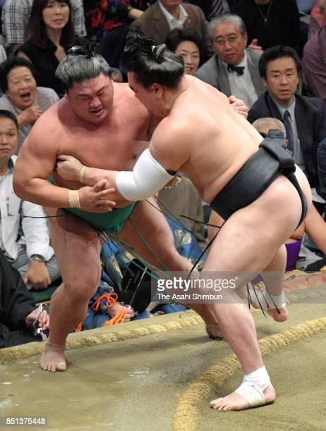Mongolian yokozuna Harumafuji pushes sekiwake Yoshikaze out of the ring to win during day thirteen of the Grand Sumo Autumn Tournament at Ryogoku...
