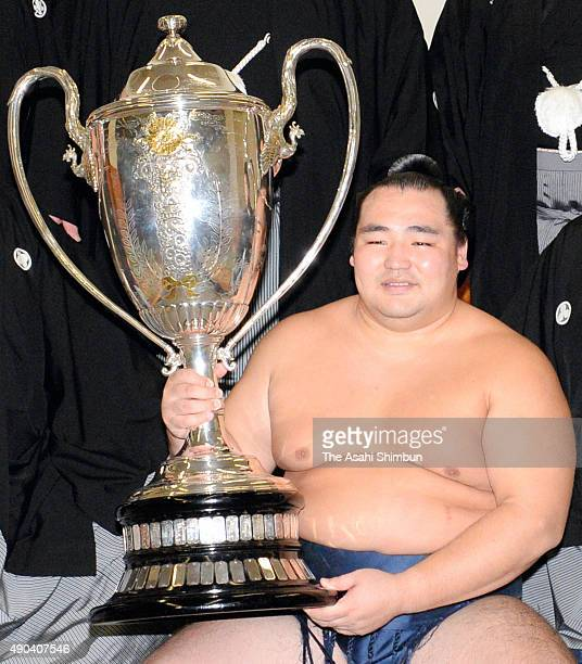 Mongolian yokozuna Kakuryu poses for photographs with the trophy in the dressing room after winning the Grand Sumo Autumn Tournament at Ryogoku...
