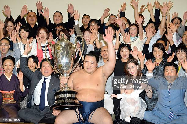 Mongolian yokozuna Kakuryu poses for photographs with withi his supporters in the dressing room after winning the Grand Sumo Autumn Tournament at...
