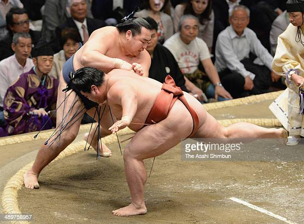 Mongolian yokozuna Kakuryu throws Yoshikaze during day two of the Grand Sumo Summer Tournament at Ryogoku Kokugikan on May 12 2014 in Tokyo Japan