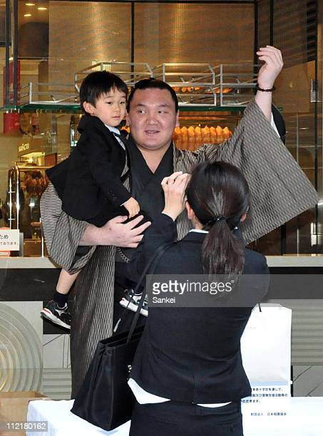 Mongolian Yokozuna sumo grand champion Hakuho poses for photographs holding a child who made a donation for the earthquake and tsunami victims at...