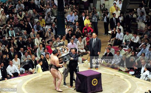 Mongolian Yokozuna, Sumo Grand Champion Hakuho receieves the trophy from Japanese Prime Minister Naoto Kan after winning the Autumn Sumo Grand...