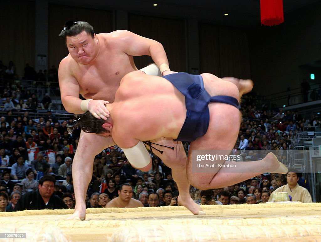 Mongolian Yokozuna, sumo's highest rank Hakuho (L) throws Georgian wrestler Tochinosin during day seven of the Grand Sumo November Tournament at Fukuoka Convention Center on November 17, 2012 in FUkuoka, Japan.