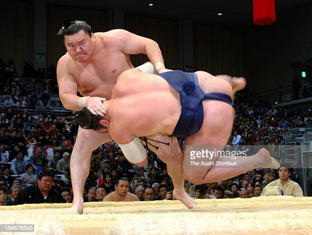 Mongolian Yokozuna sumo's highest rank Hakuho throws Georgian wrestler Tochinosin during day seven of the Grand Sumo November Tournament at Fukuoka...