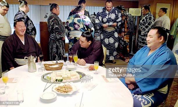 Mongolian yokozunas Hakuho Harumafuji and Kakuryu talk during a meeting on June 30 2015 in Nagoya Aichi Japan