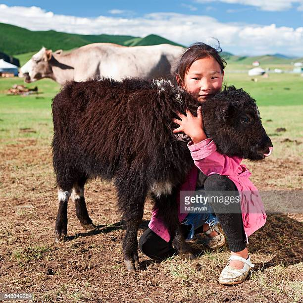 Mongolian young girl playing with yak in Central Mongolia