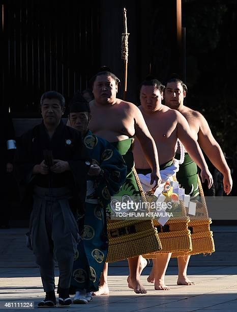 Mongolianborn sumo grand champion or 'yokozuna' Hakuho enters Meiji shrine with caller Takuro referee Shonosuke Kimura Tsuyuharai Kyokutenho and...