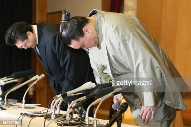 Mongolianborn yokozuna or grand champion Harumafuji and his stable master Isegahama bow during a press conference to announce Harumafuji's retirement...
