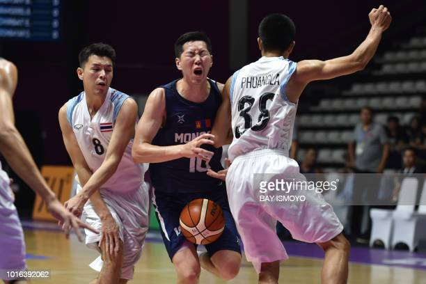 Mongolia's Bilguun Battuvshin reacts during contact with Thailand's Arnat Phuangla in their men's basketball preliminary Group A game between...