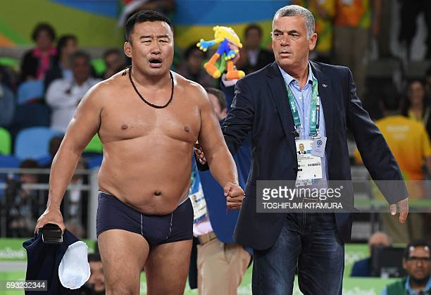 Mongolia's Mandakhnaran Ganzorig's coach reacts after the judges announced that Uzbekistan's Ikhtiyor Navruzov won following a video replay in their...
