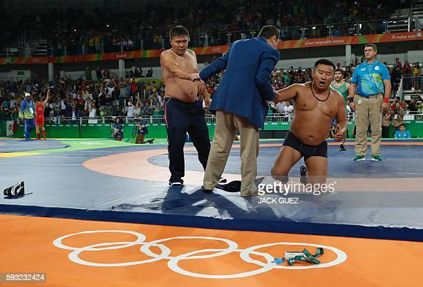 Mongolia's Mandakhnaran Ganzorig's coaches react after the judges announced that Uzbekistan's Ikhtiyor Navruzov won following a video replay in their...