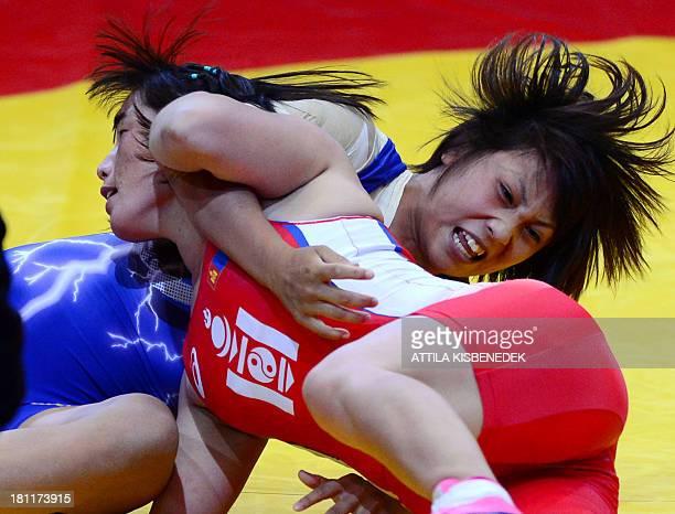 Mongolia's Munkhtuya Tungalag and Japan's Ayaka Ito fight during the women's free style 59 kg category for bronze of the FILA World Wrestling...