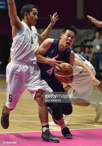 Mongolia's Sergelen Otgonbaatar attempts to break past Thailand's Sorot Sunthonsiri in their men's basketball preliminary Group A game between...