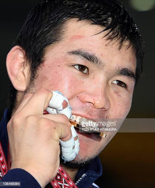 Mongolia's Tsagaanbaatar Haskhbaatar bites his gold medal after beating Iranian judoka Arash Miresmaeili in their Asian Games judo men's under 66kg...