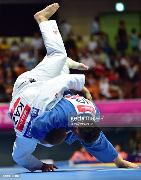 Mongolia's Tuvshinbayar Naidan competes with Kazakhstan's Maxim Rakov in the men's 100kg judo final match during the 2014 Asian Games at Dowon...