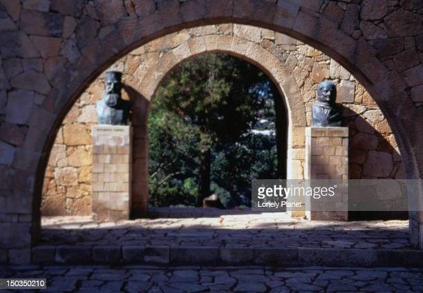 moni arkadiou, a 16th century monastery: arches display the busts of the only survivor when an explosion hit the building in 1866, and the abbot who lit the gunpowder which caused the explosion - rethymno province, crete - only men stockfoto's en -beelden