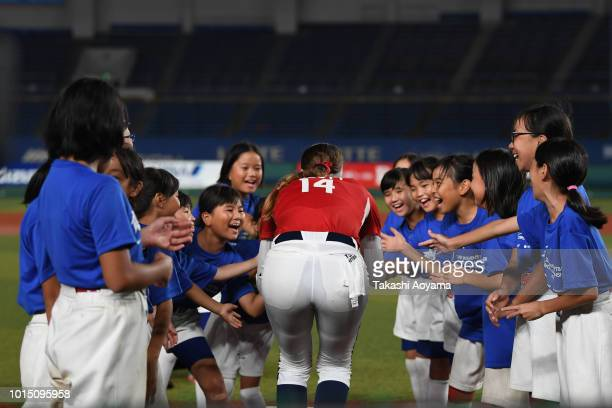 Monica Cecilia Abbott of United States high fives with kids prior to the Playoff Round match between United States and Japan at ZOZO Marine Stadium...