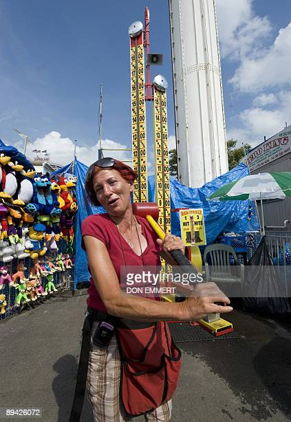 Monica Ghee who runs the 'High Striker' game in the amusement area holds a hammer as she waits for customers July 27 2009 in Coney Island NY Nearly...