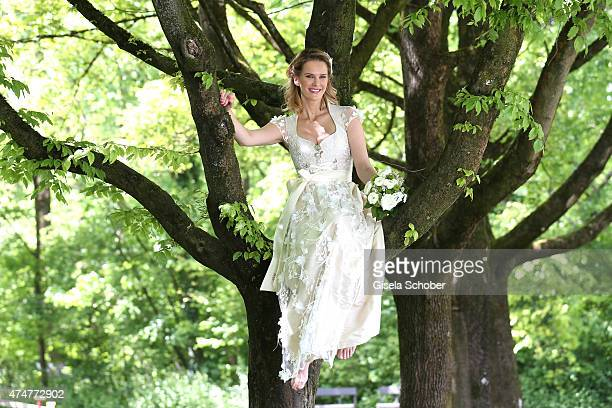 Monica Ivancan wearing a wedding dirndl by Astrid Soell poses sitting in a tree during a photo session on May 11 2015 in Munich Germany