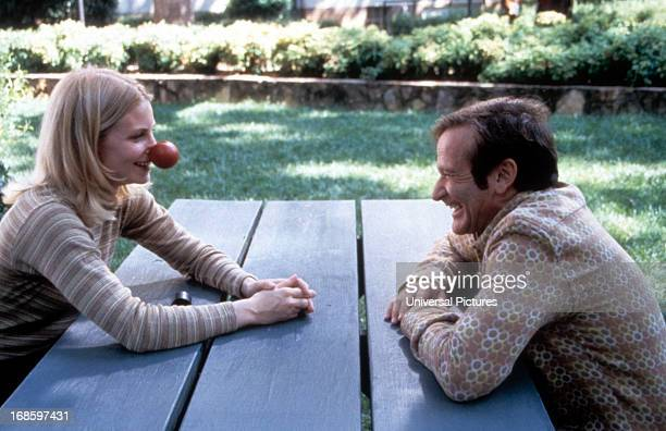 Monica Potter sits with Robin Williams in a scene from the film 'Patch Adams' 1998