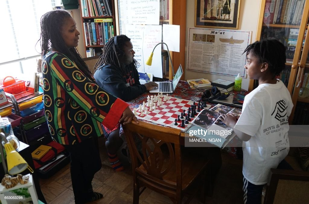 Monica Utsey, 49, is seen with her children Zion (C), 17, and Ayinde, 10, who she homeschools at her apartment in Washington, DC on February 24, 2017. / AFP PHOTO / MANDEL NGAN / With AFP Story by Margaret