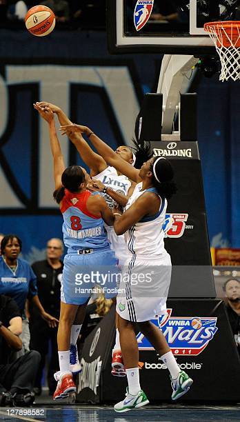 Monica Wright and Amber Harris of the Minnesota Lynx block a shot by Iziane Castro Marques of the Atlanta Dream in the first quarter of Game One of...