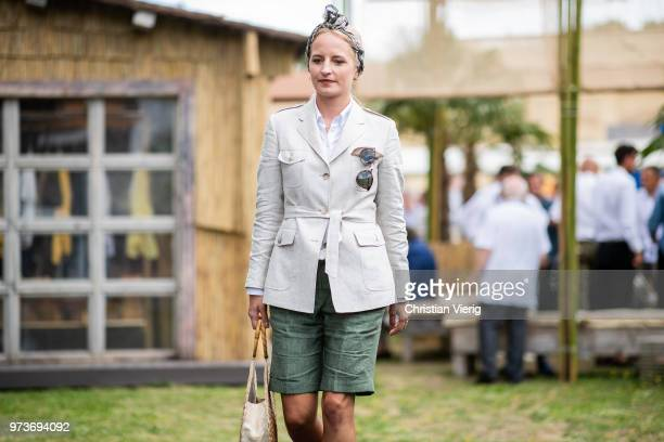 Monika Kaminska wearing round straw bag beige belted safari linen jacket with patched pockets button down shirt green bermuda shorts is seen during...