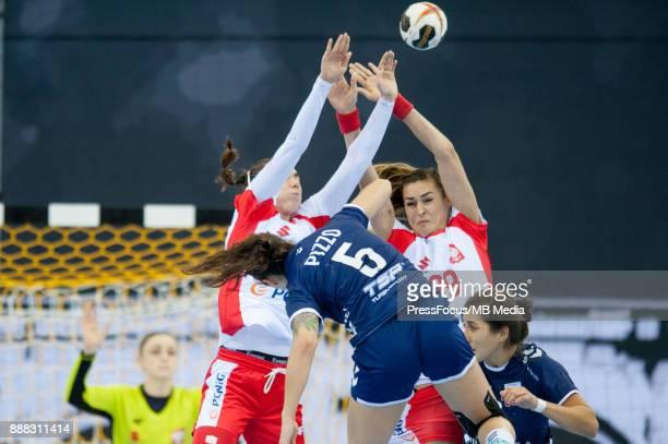 Monika Kobylinska of Poland and Kinga Achruk of Poland block a shot from Manuela Pizzo of Argentina during IHF Women's Handball World Championship...
