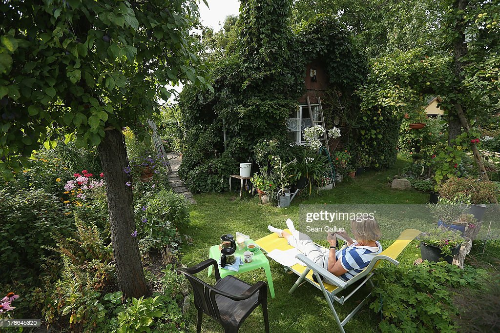 Monika, who preferred not to reveal her last name, knits on a lawnchair next to the ivy-covered cottage in the garden she and her husband Mario have leased for the last 30 years in the Oeynhausen Small Garden Association garden colony on August 29, 2013 in Berlin, Germany. At the Oeynhausen colony about 300 of its 438 gardens are currently threatened by real estate development, as are about another 24 colonies across the city. Berlin has about 900 garden colonies that are owned by the city and that provide urban dwellers who don't have land of their own the opportunity to maintain a garden and escape the stress of urban life. Berlin is currently undergoing a housing squeeze and city authorities are beginning to sell some of the colonies to developers, which has caused outrage in a city where the colonies of small gardens are a deep-seated tradition going back over a century.
