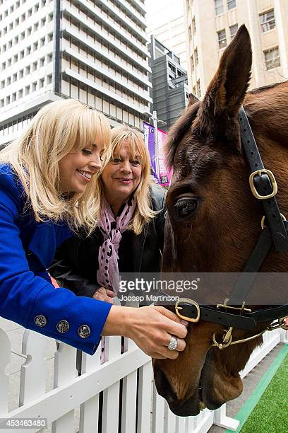 Monique Wright and Wendy Green pat Rogan Josh during the Melbourne Cup Carnival activation at Martin Place on August 11, 2014 in Sydney, Australia.