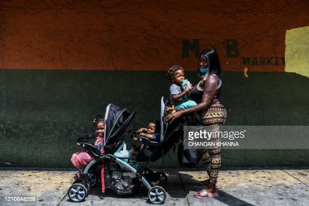 Monisha Lanir poses with her three children in a stroller at a roadside sidwalk in a low income mostly AfricanAmerican neighbourhood in Miami on...